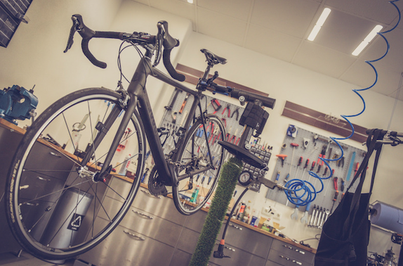 Photo of a bicycle in a repair shop by Alexander Dummer via Canva